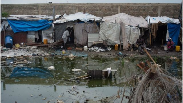 People living in temporary sheds next to a mosquito infested pond in DRC