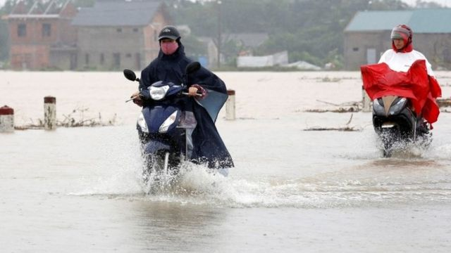 People on scooters ride through flood water in Hue city, Vietnam (05 November 2017)