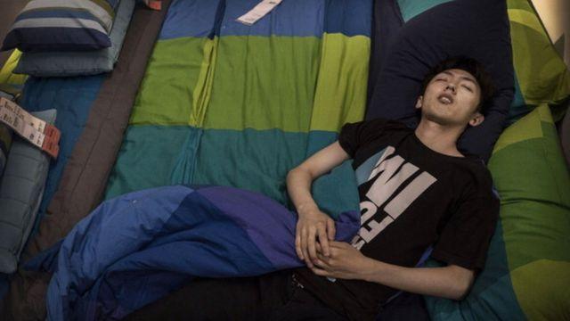 Чоловік спить у ліжку