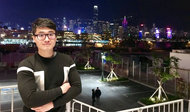 Simon Cheng stands against a city backdrop at night