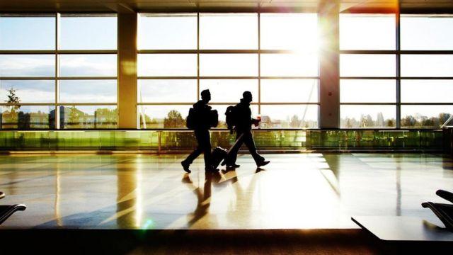 Personas caminando por un aeropuerto