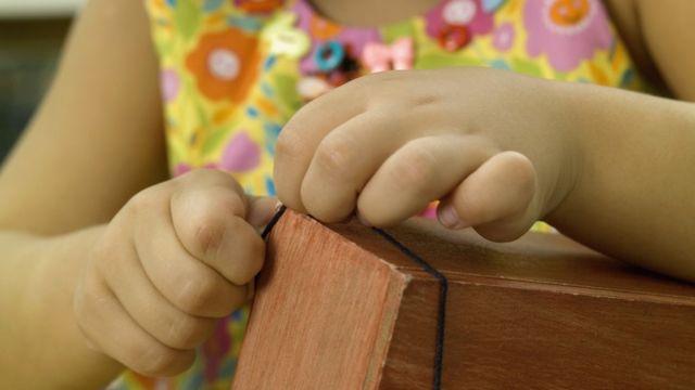 Mãos de uma menina abrindo uma caixa