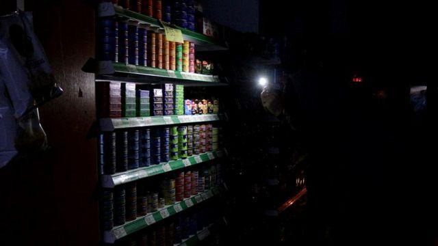 Люди используют экраны телефонов, чтобы осветить полки супермаркета в Буэнос-Айресе (Аргентина)