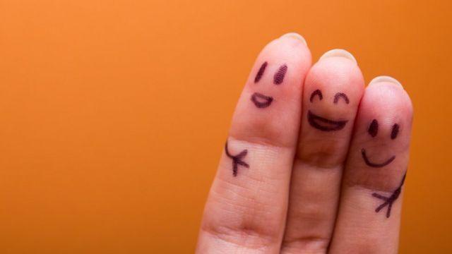 Dedos con caras pintadas abrazándose