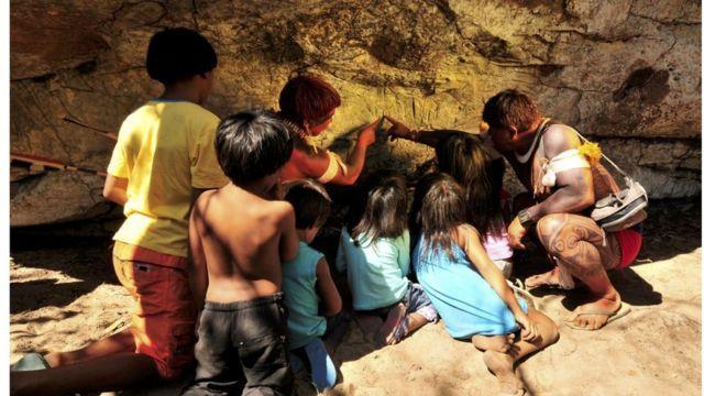 Registro de Índio waurá ensinando a mitologia em torno do guerreiro Kamukuwaká a crianças da aldeia usando as gravuras da caverna no Xingu antes do local ser vandalizado