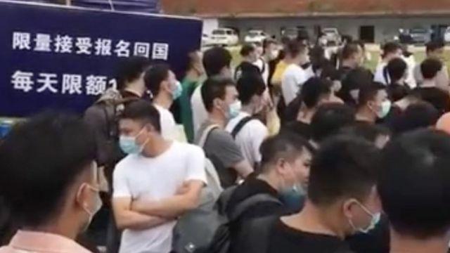 """网络画面显示很多在缅北的中国人排队等候回国。后方的标志牌写有""""限量接收报名回国""""字样。"""
