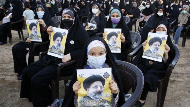 Apoiadores do candidato presidencial iraniano Ebrahim Raisi seguram fotos dele em um comício eleitoral em Eslamshahr, Irã (6 de junho de 2021)