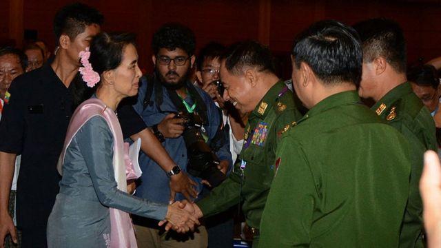20年間にわたりアウンサンスーチー氏は軍部と激しく対立してきたが、今では協力し合わなくてはならない。写真は昨年9月に首都ネピドーで開かれた平和会議の終わりに軍部の代表にあいさつするスーチー氏(2016年9月3日)
