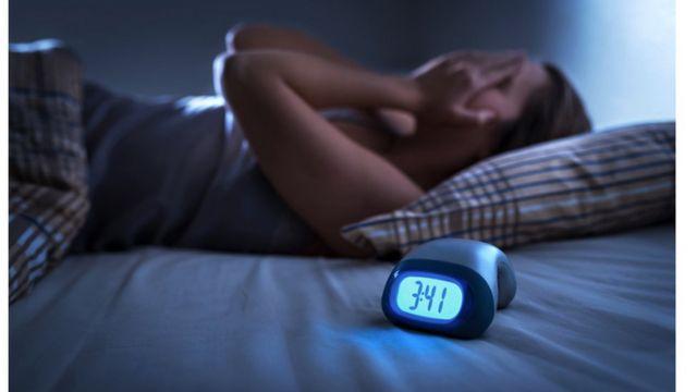 Mulher deitada na cama com o despertador tocando