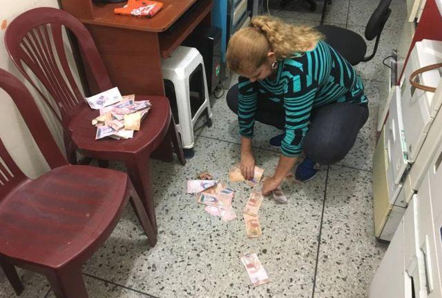 Yaneth recoge del suelo los billetes inservibles con los que ha estado jugando su nieto.