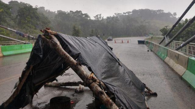 Barraca improvisada com troncos e plástico em cima de ponte e sob chuva