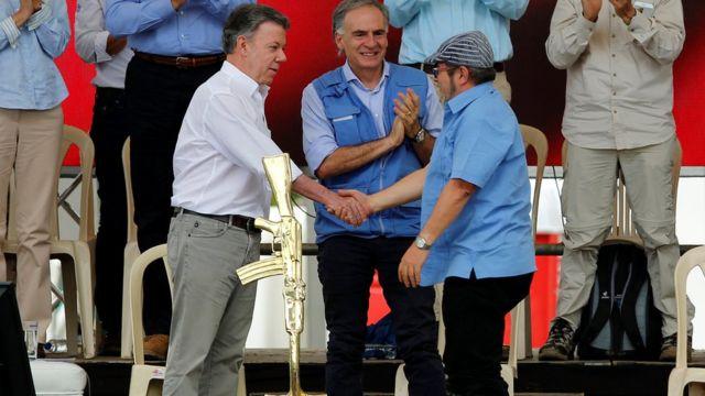 Kolombiya Cumhurbaşkanı Juan Manuel Santos ve FARC lideri Rodrigo Londoño Echeverri el sıkışırken.