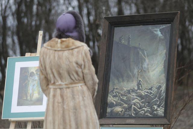 Жінка біля картин, встановлених у Бабиному Яру