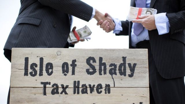 "Unseen protestors dressed as a businessman shake hands whilst holding wads of fake currency on a protest site named by participants as the ""Isle of Shady Tax Haven Poor people keep out!"" in London on June 14, 2013,"