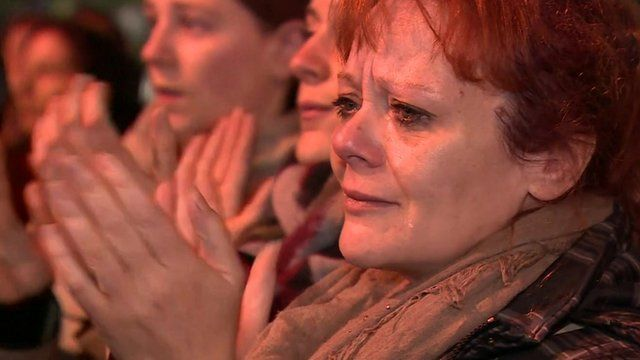 A tearful woman claps outside the Bataclan theatre in Paris