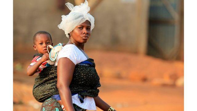 Mulher carregando criança nas costas