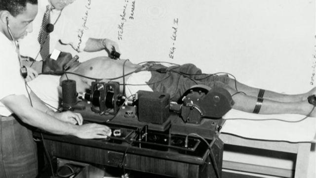 Foto em preto e branco mostra dois homens, um deles branco, usando aparelhos antigos para fazer experimentos em um homem negro deitado sem camisa