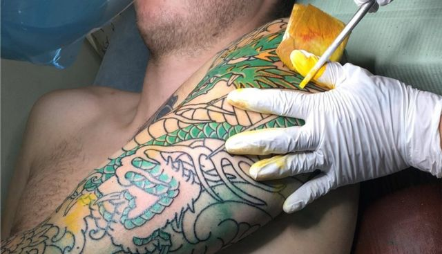 Horimitsu adds yellow ink to the tattoo using a stick tipped with needles