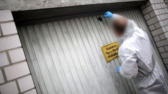 Perito busca impressões digitais no portão da garagem onde pedaços de um corpo humano foram encontradas em Schwalbach