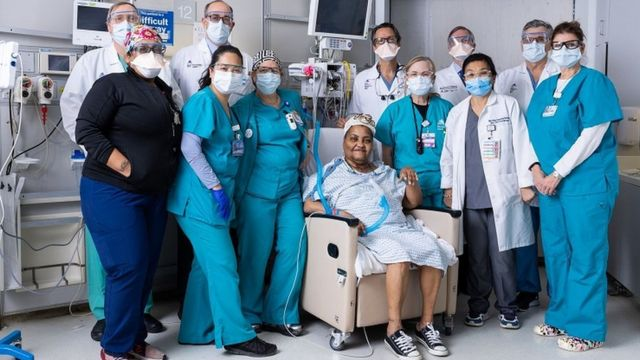 Paciente sentada e rodeada da equipe médica em ambiente hospitalar