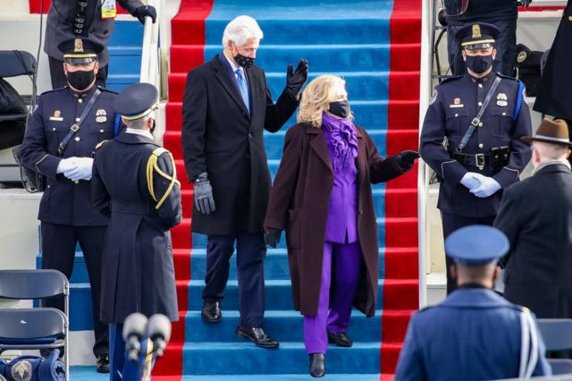 Bill Clinton and Hillary Clinton walk down steps together to find their seat