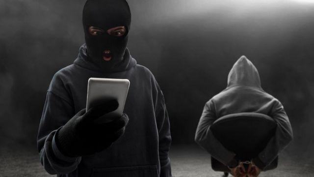 Un secuestrador con un teléfono en la mano.