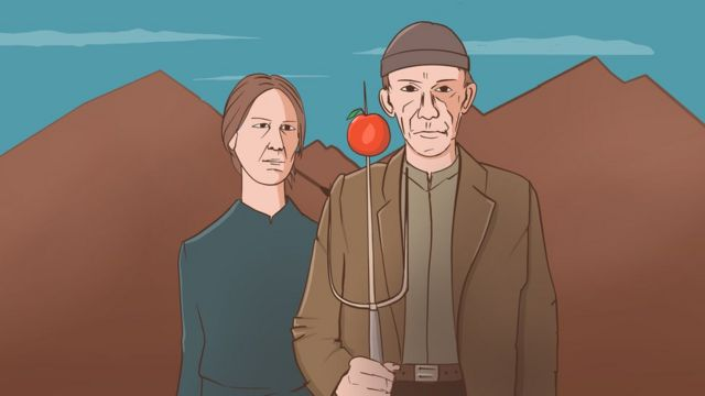 A man and a woman stand with an apple on the end of a knife