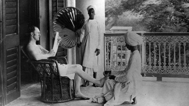 Индийский слуга делает педикюр британскому офицеру.