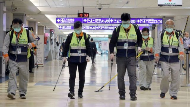 Masked workers disinfect a passenger throughfare at the Taoyuan International Airport on January 22, 2020