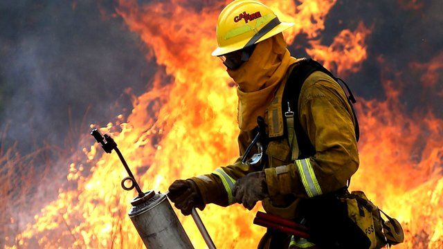 A Cal Fire firefighter moves away from a tall flame as he uses a drip torch to burn dry grass