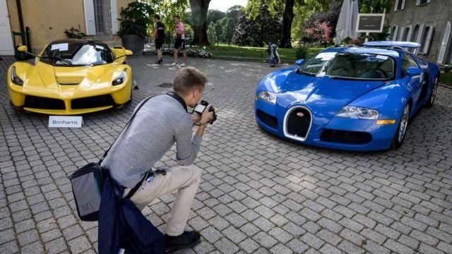Une photo prise le 28 septembre 2019 à l'abbaye de Bonmont à Cheserex, en Suisse romande, montre une Ferrari LaFerrari 2015 (G) et une Bugatti Veyron EB 16.4 Coupé 2010 lors d'une vente aux enchères en avant-première par la maison de vente Bonhams de voitures de sport appartenant au fils du président de la Guinée équatoriale.