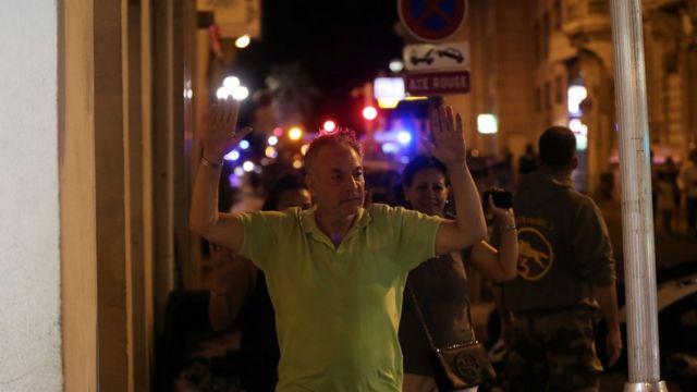 Varios ciudadanos caminan con las manos en alto ante un punto de control policial
