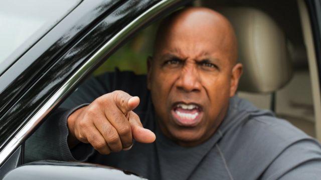 Un conductor molesto gritando algo.