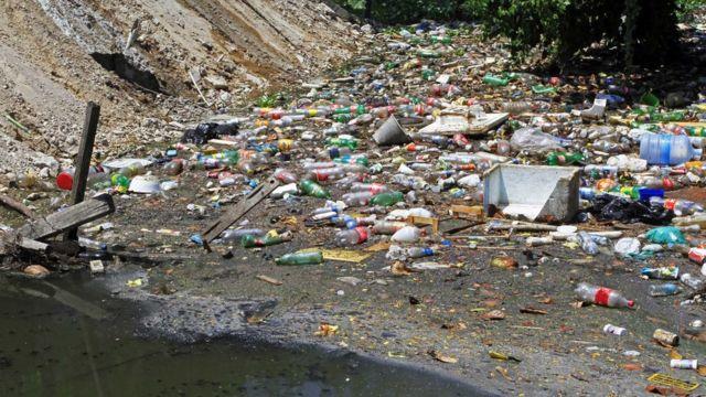 Lixo espalhado em terreno aberto em dia de sol