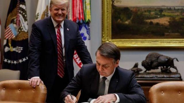 Trump sorrindo, de pe atras da cadeira onde Bolsonaro esta sentado assinando um documento