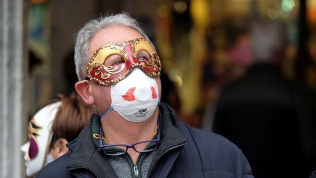 A masked carnival reveller wears protective face mask at Venice Carnival