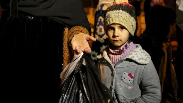 A Syrian girl waits with her family after an aid convoy entered Madaya, Syria January 11, 2016