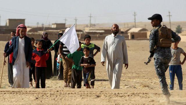 मोसुल के एक नज़दीक एकक गांव से सफेद झंडा लेकर निकले ग्रामीण सुरक्षा बलों से संपर्क करते हुए.