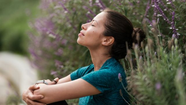 mujer respirando junto a unas flores