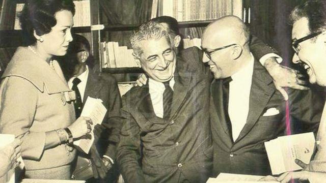 Foto em preto e branco mostra Gilberto Freyre sorrindo entre livros e amigos na Livraria São José
