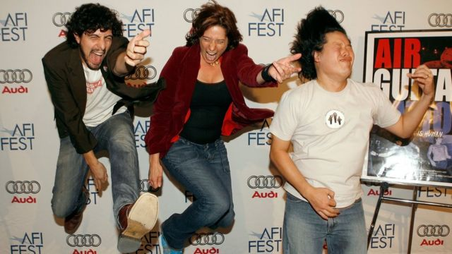 """Tres personas tocando """"guitarra de aire"""""""