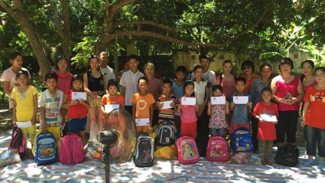 Amie (áo hồng thứ hai hàng trên từ trái) cùng gia đình tặng quà cho trẻ em khó khăn ở Việt Nam hồi 2015