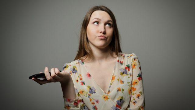 Mujer con un teléfono en la mano.
