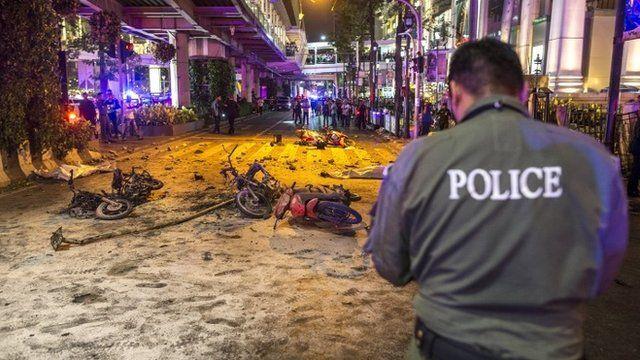 Police officers inspect the scene of an explosion near Erawan Shrine, central Bangkok