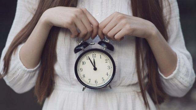 Mulher com relógio na mão
