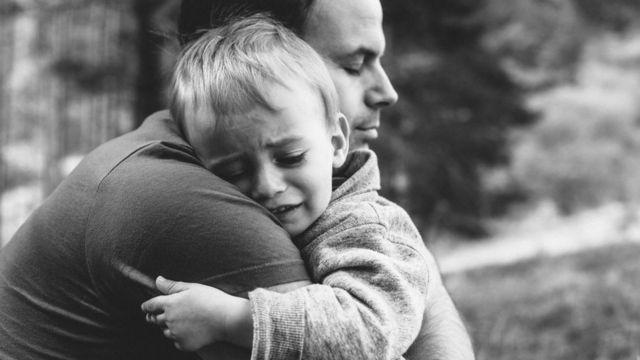 Un padre con su hijo llorando