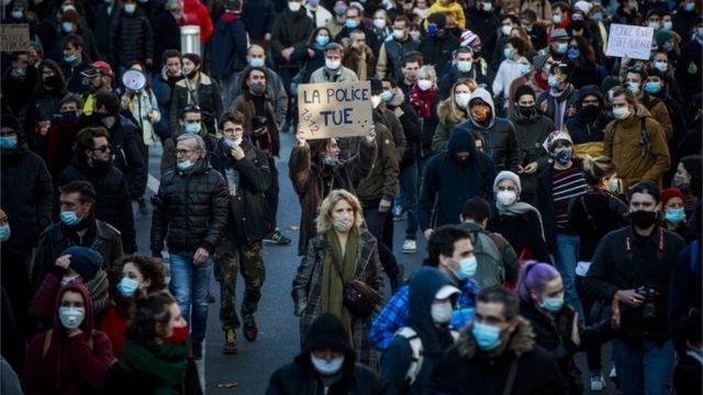 """فردی کاغذنوشته """"پلیس میکشد"""" را در اعتراض به قانون امنیتی جدید فرانسه در دست گرفته است"""
