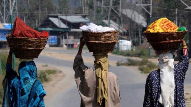 માથા પર ટોપલા લઈને જતી મહિલાઓ