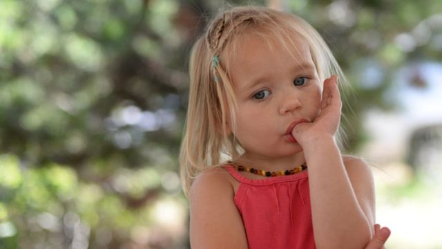 young girl sucking her thumb