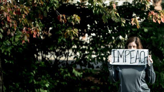 Woman wey carry sign wey dem write impeach